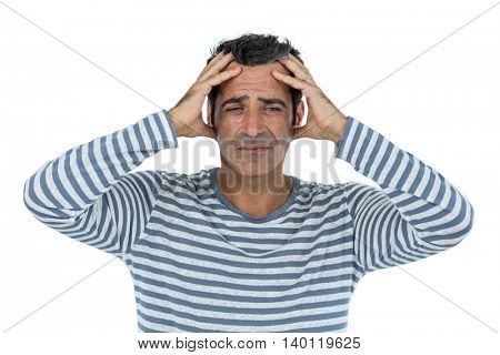 Mid adult man suffering from headach against white background