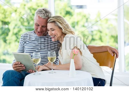 Smiling mature couple using digital tablet with wine on table at restaurant
