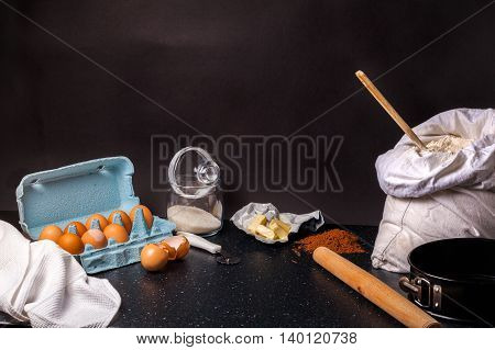 Ingredients for baking. Shortbread dough. Eggs, flour, butter, sugar on black table and dark background. Background layout with free text space.
