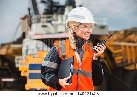 Beautiful young ingineer talking on the radio