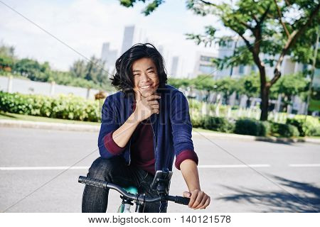 Joyful young man enjoying cycling in the city