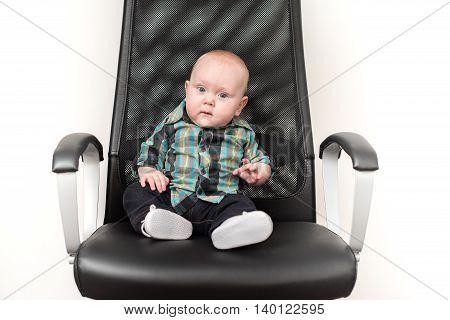 Little baby boy sitting on big chair like a boss