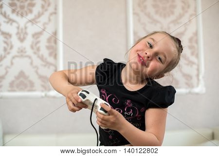 cute little girl sitting on the couch and playing video games with joystick