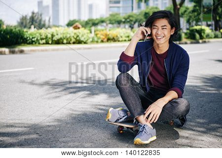 Portrait of young man sitting on skateboard and talking on phone