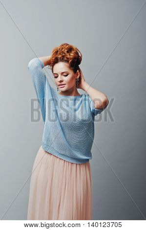Studio Portrait Of Young Red Haired Curly Girl At Blue Blouse And Pink Skirt