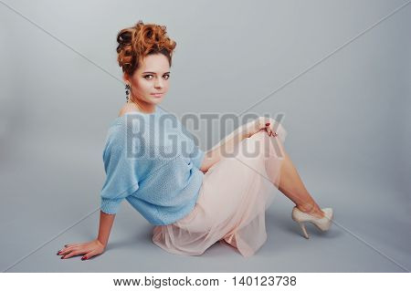 Studio Portrait Of Lying Young Red Haired Curly Girl At Blue Blouse And Pink Skirt