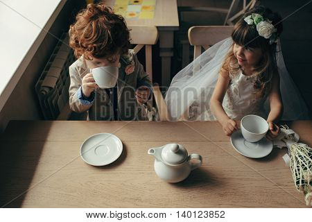 happy boy and girl having tea party in cafe