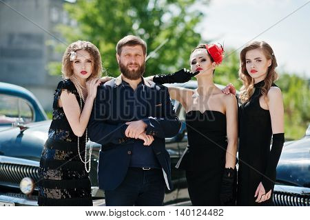 Three young girl in retro style dress with beard man boss background old classic vintage cars