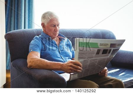 Senior man seated on a sofa reading newspaper