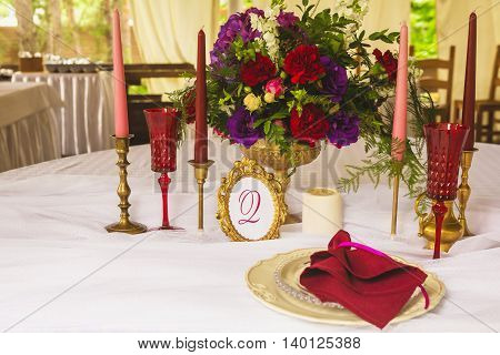 Festive wedding table setting with pink flowers, red napkins, vintage cutlery and candles, bright summer table decor. Plates, forks and knifes for wedding dinner