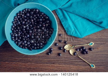 Freshly picked blueberries in a blue bowl. Juicy and fresh blueberries on wooden table. Bilberry on wooden Background. Blueberry antioxidant. Concept for healthy eating and nutrition. Top view.
