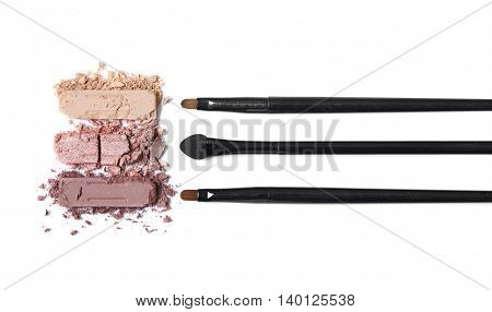 Broken neutral eye shadow palette with make up brushes isolated on a white background