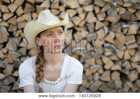 young girl in a cowboy hat on a background of wood pile