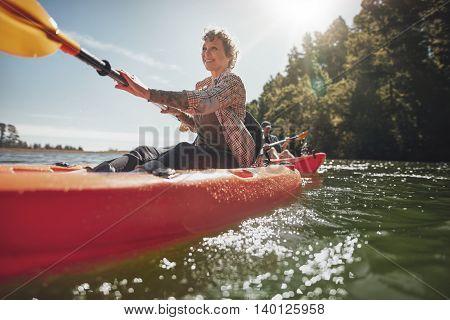 Shot of senior woman canoeing in lake on a summer day. Mature woman paddling a kayak in lake.