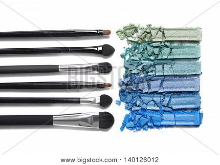 Broken blue and green eyeshadow palette with make up brushes isolated on a white background