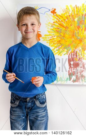 Cute smiley boy draws a picture. over white