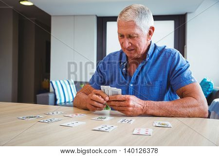 Senior man playing cards in a retirement home