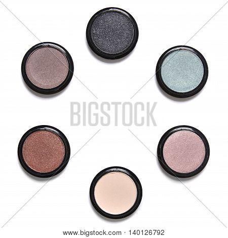 Individual eyeshadow make up pots arranged in a circle and isolated on a white background