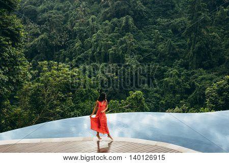 Beautiful Woman Walking On Edge Of Infinity Pool