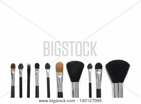 Assorted make up brushes isolated on a white background to form a page border