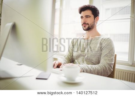 Confident businessman working on computer in creative office