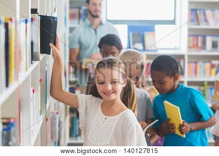Portrait of smiling girl removing book from bookshelf in library at elementary school