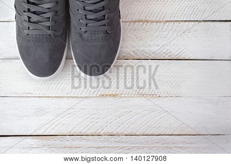 A pair of new stylish Skateboard shoes for men in grey color on white wooden background