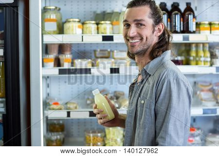Portrait of happy man shopping for groceries in supermarket