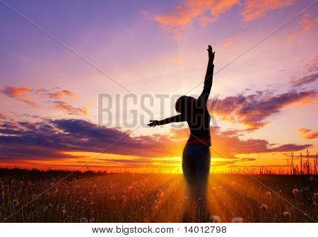 Young woman's silhouette over pink sunset light