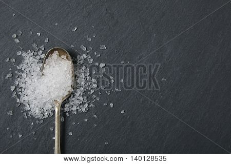 A silver spoon full of salt on a rustic slate background forming a page border