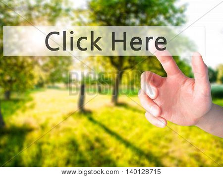 Click Here - Hand Pressing A Button On Blurred Background Concept On Visual Screen.