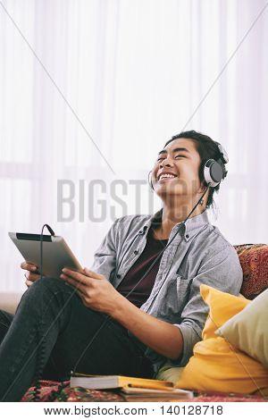 Young man in headphones enjoying music in his digital tablet