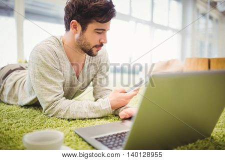 Young businessman lying on carpet while using laptop and mobile phone in creative office