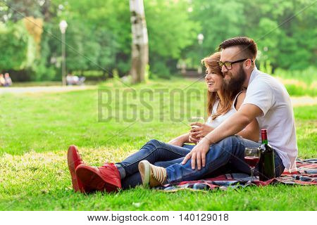 Couple in love sitting on a picnic blanket in a park holding glasses of wine hugging and enjoying their time together