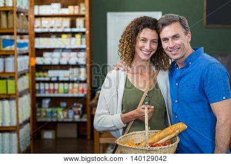 Portrait of happy couple standing with a basket in supermarket