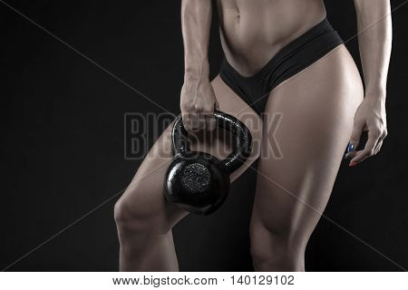 Woman holding heavy kettlebell closeup on black background