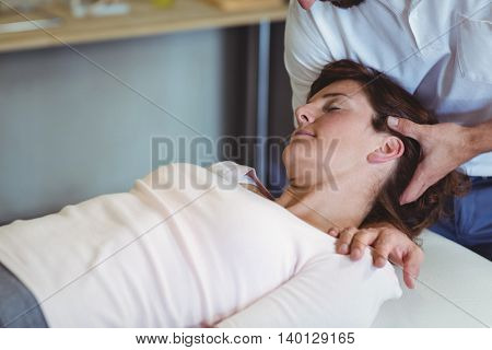 Physiotherapist giving head massage to a woman in clinic