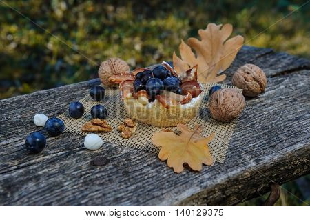 Romantic autumn still life with basket cake, walnuts, blackthorn berries and leaves, in cold colors