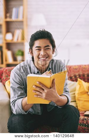 Smiling Asian student reading book at home