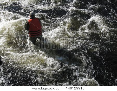 Man in the life vest standing in the water of the mountain river