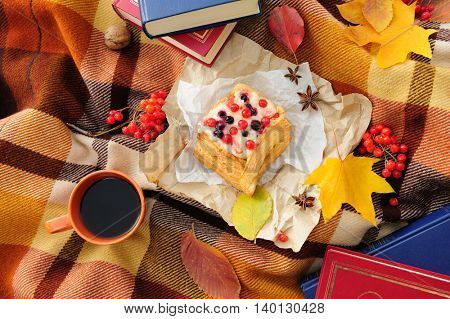 Romantic autumn still life with books, plaid, cake, coffee cup and leaves, top view