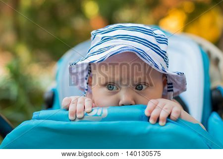 cute baby peeking out of a stroller