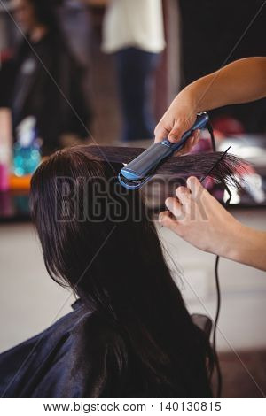 Hairdresser straightening the hair of a client at a salon