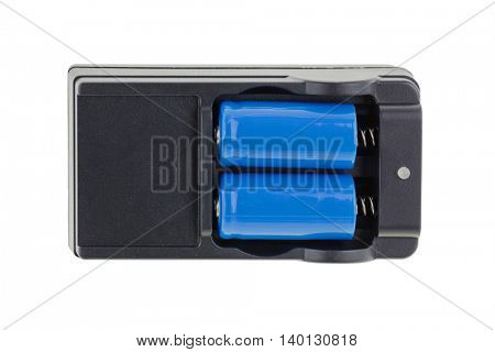 Closeup of blue Lithium battery, with its black charger isolated on white background