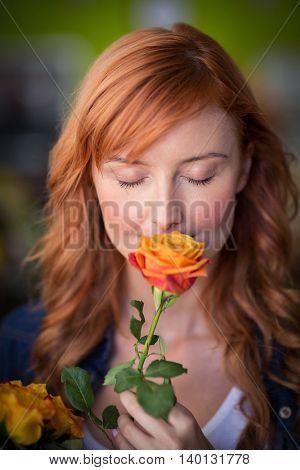 Female florist smelling a rose flower in the flower shop