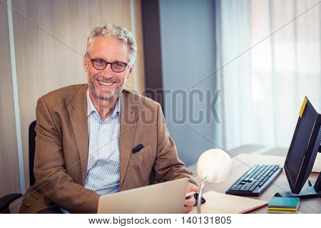 Portrait of businessman smiling in office