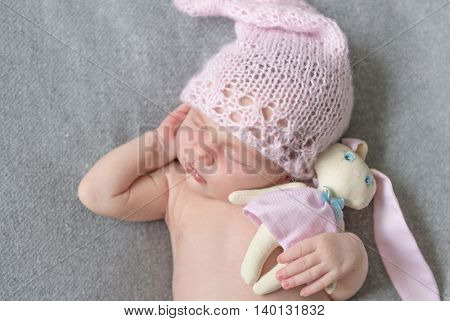 beautiful sleeping newborn girl with a toy close-up