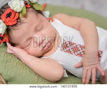 newborn girl in Ukrainian costume sleeping close-up