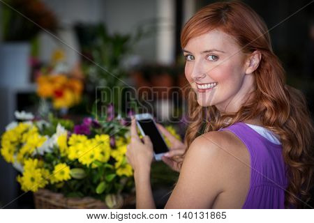 Female florist taking photogrpah of flower basket in the flower shop