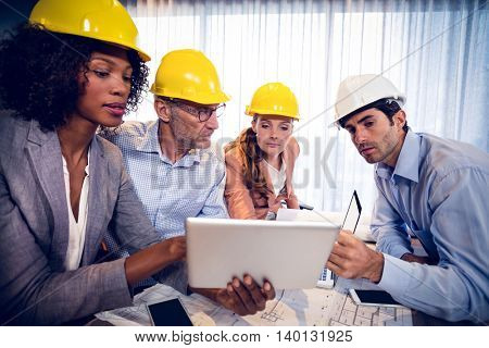Architects discussing over digital tablet during meeting in office